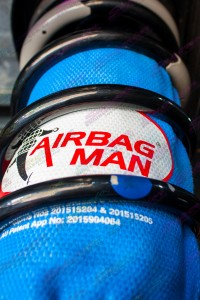 Closeup view of the airbag man coil helper and kevlar protection bag inside some black coil springs