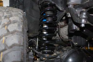 Closeup view of a black coil spring fitted to a Nissan Patrol