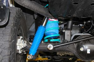 Closeup underside view of the GU Nissan Patrol showing a single Airbag Man airbag, Dobinsons coil spring, Superior coil retainer and Superior remote reservoir shock