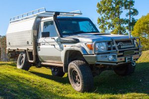 Front right view of a Silver Single Cab 79 Series Toyota Landcruiser testing out flex after being fitted with a heavy duty rear coil conversion kit