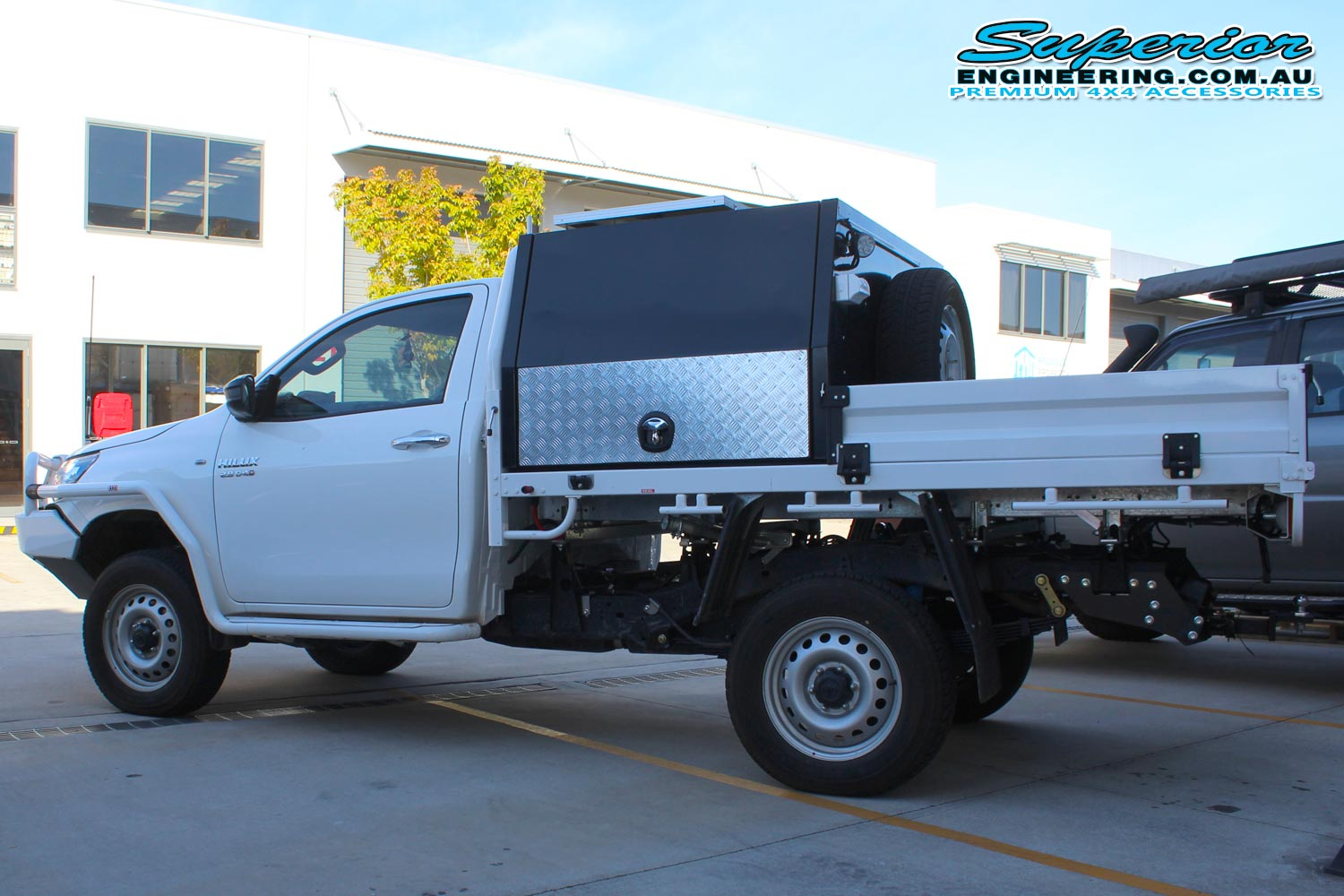 Left side view of a white Toyota Hilux Revo (single cab) fitted with a 2 inch Airbag Man leaf spring helper kit and Dual air control kit