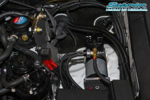 Closeup view of the Airbag Man digital dual air control kit, air compressor, air hoses, air fittings, hardware, ties and wires fitted to a single cab Toyota Hilux Revo