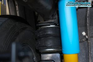 Closeup view of a single heavy duty Firestone airbag and mounts fitted between the chassis and leaf spring on the single cab Toyota Hilux Revo