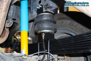 Closeup view of a single Airbag Man heavy duty Firestone airbag, mounting brackets and air hoses fitted to the chassis and leaf spring on the single cab Toyota Hilux Revo