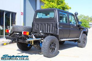 """Rear right view of a Black Toyota 79 Series Landcruiser Dual Cab after fitting a Superior Remote Reservoir 2"""" Inch Lift Kit with Airbag Man Leaf Air Kit"""