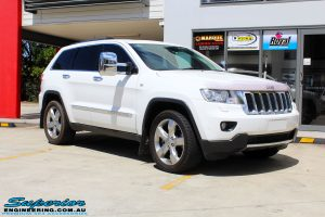 Right front side view of a White Jeep WK2 Grand Cherokee being fitted with an Airbag Man Coil Helper Air Kit Standard Height
