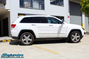 Right side view of a White Jeep WK2 Grand Cherokee being fitted with an Airbag Man Coil Helper Air Kit Standard Height