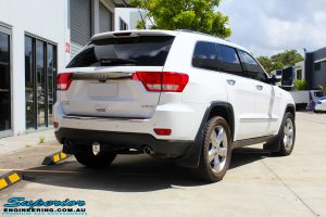 Rear right view of a White Jeep WK2 Grand Cherokee being fitted with an Airbag Man Coil Helper Air Kit Standard Height
