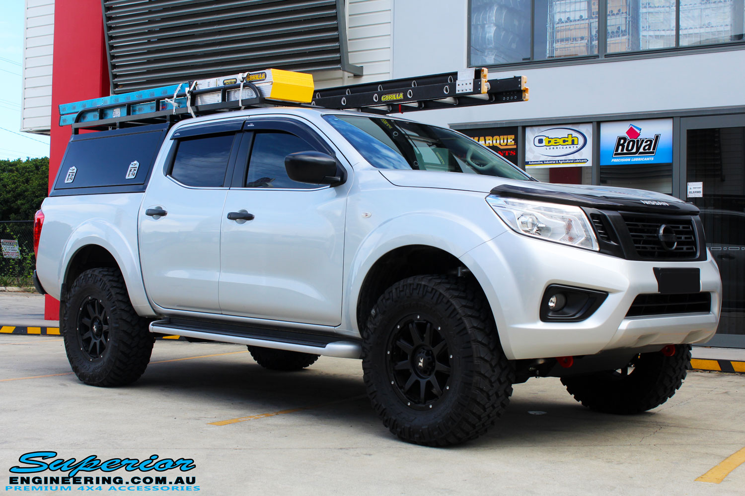 "Right front side view of a Grey Nissan NP300 Navara Ute after fitment of a Superior Nitro Gas 4"" Inch Lift Kit + Airbag Man 2"" Coil Air Kit Helper, Ironman 4x4 Flomax Air Compressor and Nitto Trail Grappler Tyres with King Gator Wheels"