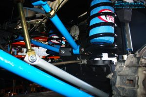 Left side view of under the tray after fitment showing Remote Reservoir Shock, Coil Spring with Airbag Man Coil Helper and Lower & Upper Control Arms.