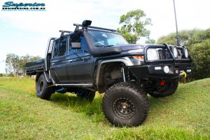 """Front right side view whilst flexing of a Grey Toyota 79 Series Landcruiser Dual Cab after fitment of a Superior 4"""" Inch Rear Coil Conversion Kit with Hyperflex Radius Arms, Remote Reservoir Shocks and a Airbag Man 4"""" Inch Coil Helper Air Kit."""