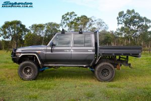 "Left side view of a Grey Toyota 79 Series Landcruiser Dual Cab after fitment of a Superior 4"" Inch Rear Coil Conversion Kit with Hyperflex Radius Arms, Remote Reservoir Shocks and a Airbag Man 4"" Inch Coil Helper Air Kit."
