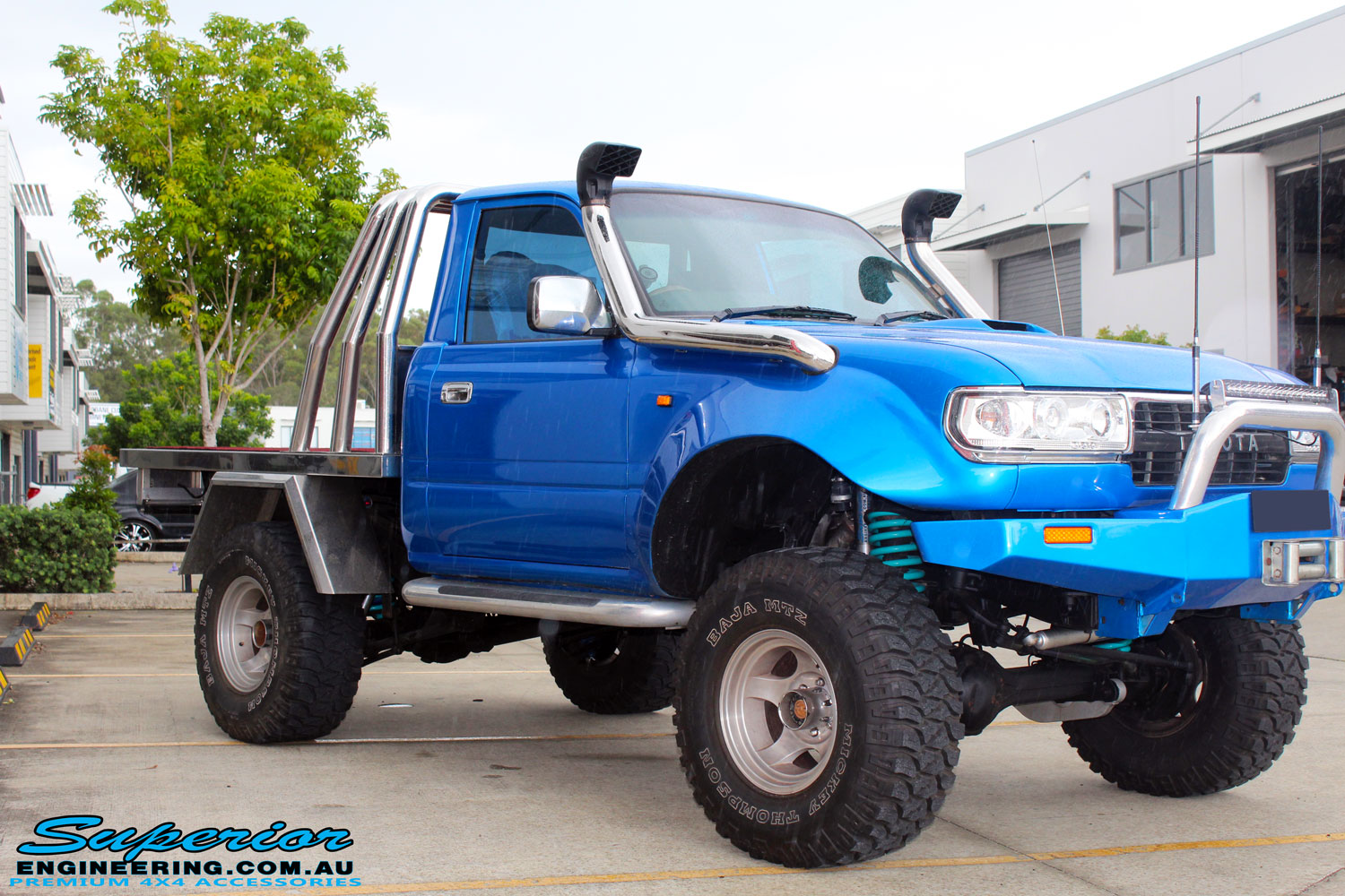 "Left front side view of a Blue Toyota 80 Series Landcruiser Ute Chop after fitment of a Airbag Man 4"" Inch Coil Air Helper Kit"