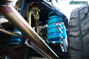 Left mid rear up close view of the fitted Superior Lower Control Arm, Coil Spring with Airbag Man Coil Air Kit and Sway Bar Kit