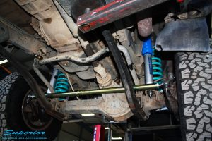 Mid underbody view looking front on of the fitted Superior Tie Rod Bar, Nitro Gas Shocks + Coil Springs