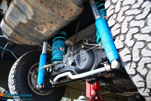 """Right side rear view of the fitted Superior Coil Conversion 2"""" Inch Rear Kit containing Remote Reservoir Shocks, Coil Springs, Swar Bar Kit, + Airbag Man Coil Air Kit Helper"""