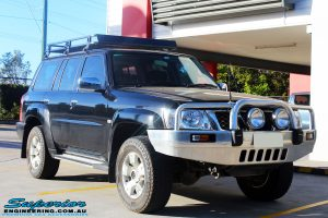 """Right front side view of a Black Nissan GU Patrol Wagon being fitted with a Superior 2"""" Inch Nitro Gas Lift Kit, Airbag Man 2"""" Inch Coil Air Helper Kit, Safari Snorkel, Brown Davis Long Range Fuel Tank, Superior Coil Tower Brace Kit & Superior Upper Control Arms"""