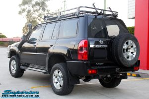 """Rear left view of a Black Nissan GU Patrol Wagon after being fitted with a Superior 2"""" Inch Nitro Gas Lift Kit, Airbag Man 2"""" Inch Coil Air Helper Kit, Safari Snorkel, Brown Davis Long Range Fuel Tank, Superior Coil Tower Brace Kit & Superior Upper Control Arms"""