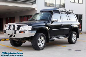 """Left front side view of a Black Nissan GU Patrol Wagon after being fitted with a Superior 2"""" Inch Nitro Gas Lift Kit, Airbag Man 2"""" Inch Coil Air Helper Kit, Safari Snorkel, Brown Davis Long Range Fuel Tank, Superior Coil Tower Brace Kit & Superior Upper Control Arms"""
