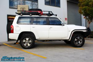 """Right side view of a Nissan GU Patrol Wagon in White fitted with a Airbag Man Coil Air Kit 3"""" Inch Lift Kit & Superior Tie Rod Comp Spec 4340m Solid Bar whilst on the hoist at Superior"""