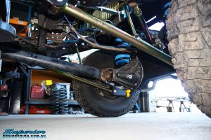 """Left side on underbody shot of the fitted Superior 2"""" Inch Coil Conversion Rear Kit containing Shocks, Coil Springs, Swar Bar Kit, + Airbag Man Coil Helper Air Kit"""