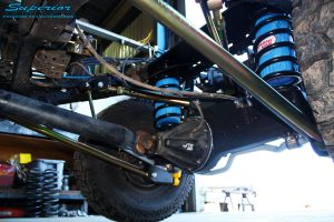 """Left side close up underbody shot of the fitted Superior 2"""" Inch Coil Conversion Rear Kit containing Shocks, Coil Springs, Swar Bar Kit, + Airbag Man Coil Helper Air Kit"""