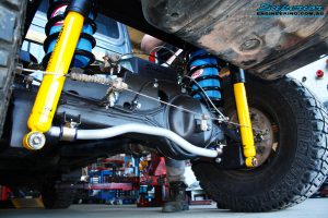 """Rear left underbody shot of the fitted Superior 2"""" Inch Coil Conversion Rear Kit containing Shocks, Coil Springs, Swar Bar Kit, + Airbag Man Coil Helper Air Kit"""