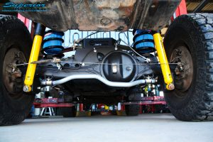 """Rear mid underbody shot of the fitted Superior 2"""" Inch Coil Conversion Rear Kit containing Shocks, Coil Springs, Swar Bar Kit, + Airbag Man Coil Helper Air Kit"""