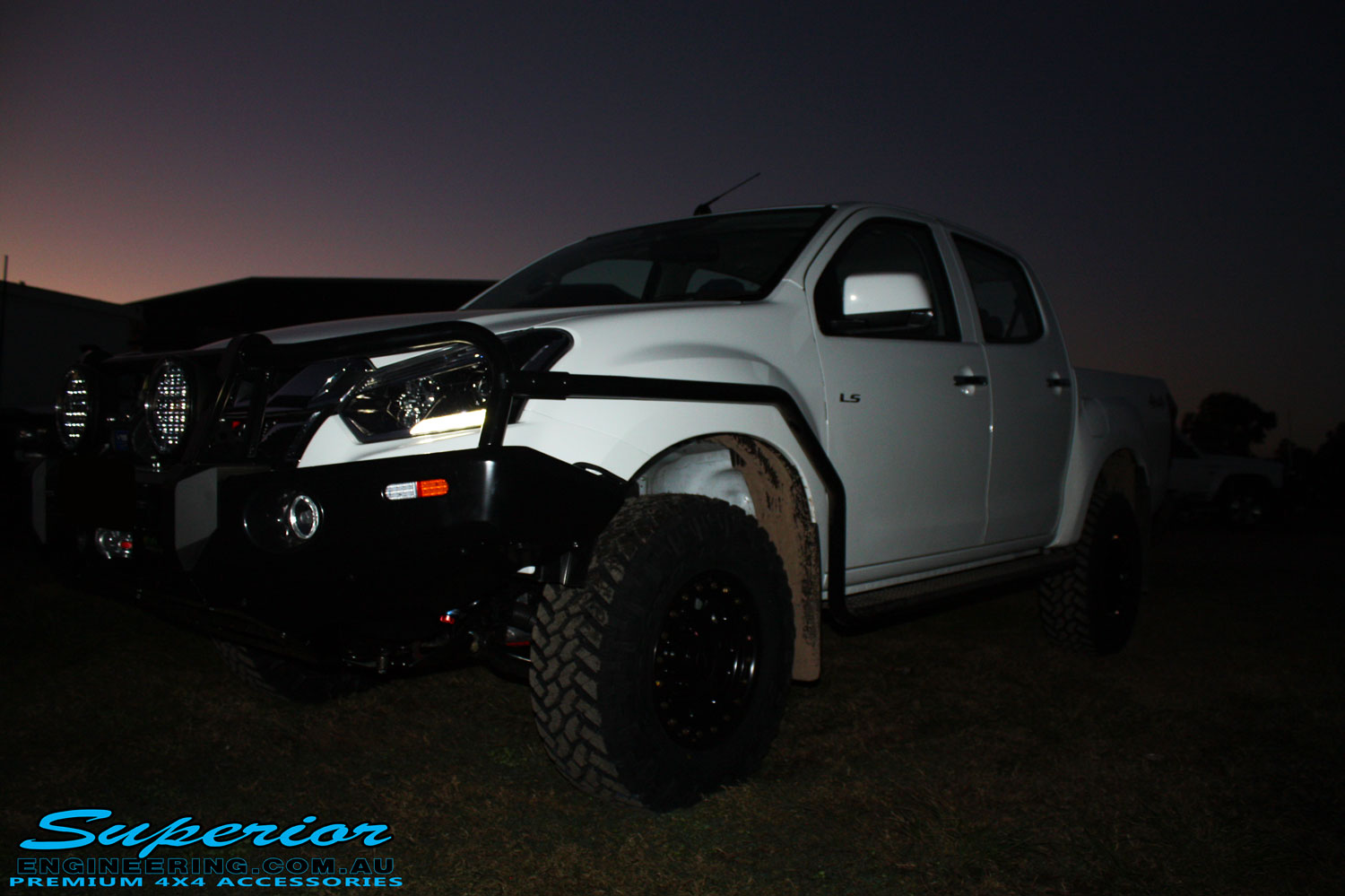 "Right front side view of a White Isuzu D-Max Dual Cab after being fitted with a Superior Remote Reservoir 2"" Inch Lift Kit, Airbag Man Leaf Air Kit, Ironman 4x4 Bullbar + Side Steps, VRS Winch, Safari Snorkel + King Wheels & Nitto Tyres"