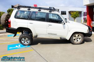 """Right side view of a flexed White Nissan GU Patrol Wagon after fitment of a Superior Nitro Gas 2"""" Inch Lift Kit, Coil Tower Brace Kit, Superior Hybrid Superflex Radius Arms, Airbag Man Coil Air Kit and Superior Adjustable Hollow Bar Drag Link"""