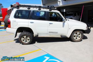 "Right side view of a flexed White Nissan GU Patrol Wagon before fitment of a Superior Nitro Gas 2"" Inch Lift Kit, Coil Tower Brace Kit, Superior Hybrid Superflex Radius Arms, Airbag Man Coil Air Kit and Superior Adjustable Hollow Bar Drag Link"