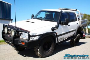 Left front side view of a White Nissan GU Patrol flexing after fitment of a range of Superior and various other brands suspension components