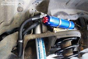 """Close up shot inside the left guard of the fitted Superior 3"""" Remote Reservoir Front Shock with Coil Spring"""
