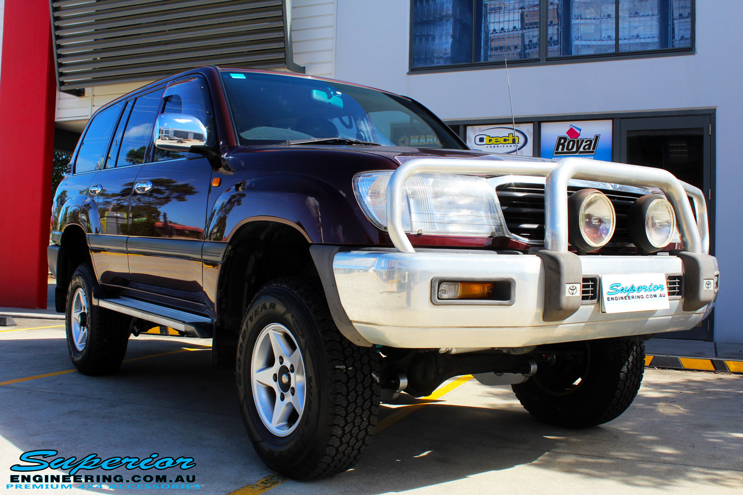 "Right front side view of a Maroon Toyota 105 Series Landcruiser Dual Cab after fitment of a Superior Nitro Gas 3"" Inch Lift Kit with Airbag Man 3"" Coil Air Kit"