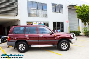 "Left side view of a Maroon Toyota 105 Series Landcruiser Dual Cab before fitment of a Superior Nitro Gas 3"" Inch Lift Kit with Airbag Man 3"" Coil Air Kit"