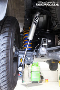 Rear left underbody view of the fitted Rear Fox 2.0 Performance Series IFP Shock, Coil Spring, Airbag Man Coil Helper Air Kit with U-Bolt Kit and Shackles
